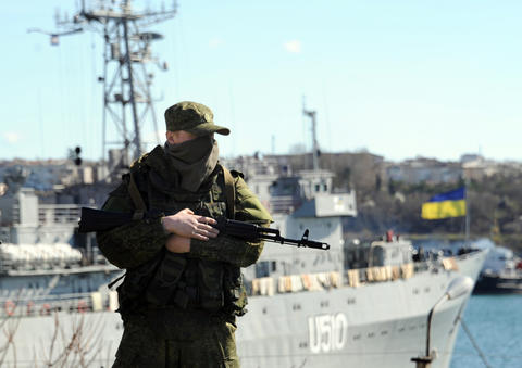 A member of the Russian troops stands guard near the Ukrainian navy ship Slavutich in the harbor of the Ukrainian city of Sevastopol. The Ukrainian flag can be seen in the background.