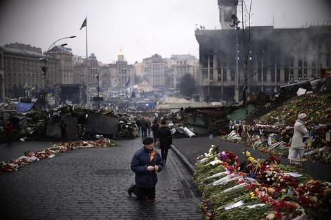 A man prays at  Independence square in central Kiev.
