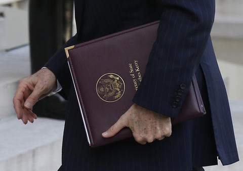 Secretary of State John Kerry carries documents as he arrives to attend the joint Declaration and Meeting of the International Support Group for Lebanon at the Elysee Palace in Paris.