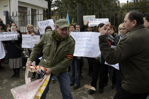 A man wearing a pro-Russia ribbon removes a placard during an anti-war picket in the Crimean city of Simferopol.