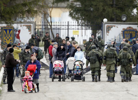Local residents and armed men believed to be Russian servicemen walk in front of the gates of a Ukrainian military unit in the village of Perevalnoye outside Simferopol.
