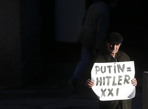 A protestor holds a banner against Russian President Vladimir Putin in front of the foreign ministry in Madrid before a meeting between Foreign Minister Sergei Lavrov and Spanish counterpart Jose Manuel Garcia-Margallo.