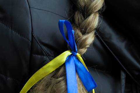 A woman wears a ribbon in Ukraine's national colors around her braid in Kiev.