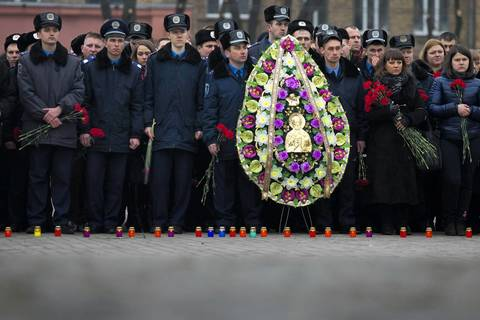 Police officers commemorate colleagues who died during recent street battles as they gather outside the police academy in Kiev.
