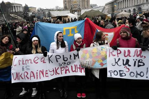 "People hold placards reading ""Crimea is Ukraine"" and a map of Ukraine during a rally on Independence Square in Kiev."