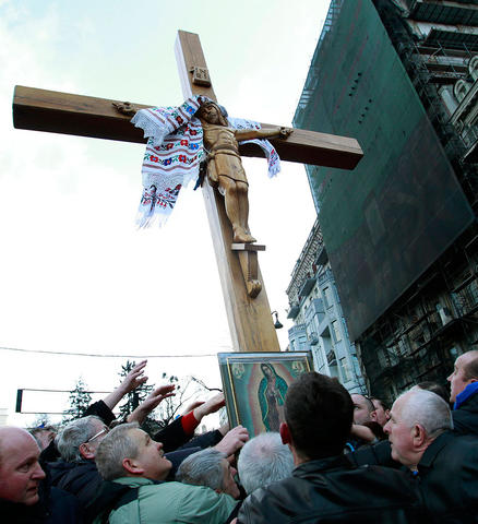 People erect a cross during a religious service at the site of the recent clashes in Kiev.