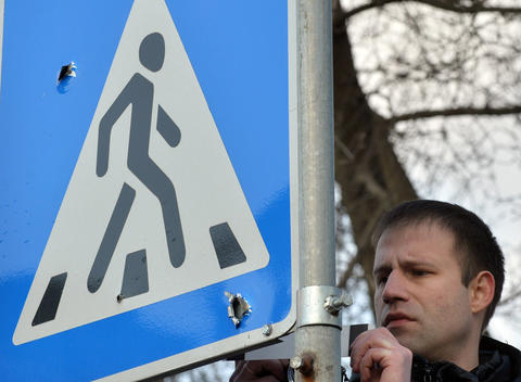 A police expert examines a road sign with bullet holes in it during a police investigation in Kiev after clashes between police and anti-government activists.