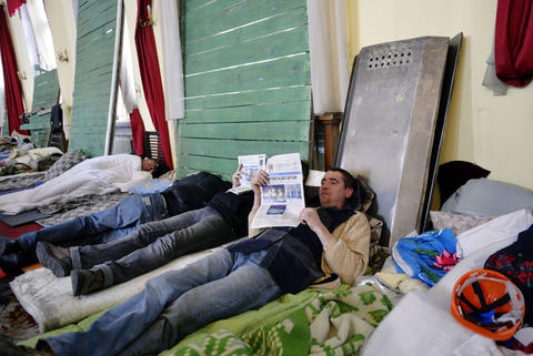 People rest in the town hall of Kiev. The hall has been the logistics, health, food and recreation center for protestors since the beginning of anti-government demonstrations.