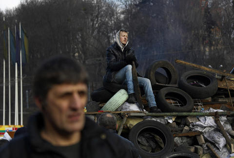 An anti-Yanukovich protester sits atop a barricade in Kiev's Independent Square.