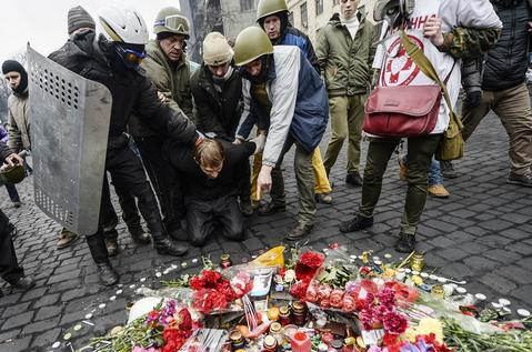 A man (C) suspected of being a sniper and member of the pro-government forces is forced by anti-government protestors to pay his respects to a mourning place of a victim killed in the recent clashes in Kiev.