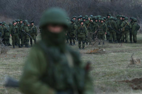 Troops under Russian command assemble before getting into trucks near the Ukrainian military base they are blockading.