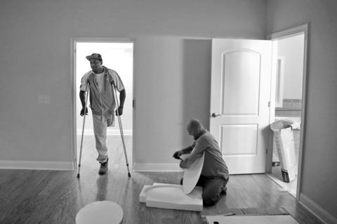 Johnathan Jackson, left, talks with Tom Thorpe as he completes the finishing touches on the master bedroom inside Jackson's newly built home. Jackson lost his leg in Afghanistan after doctors say he was exposed to an unknown toxin. Homes for Our Troops built Jackson a house and he take the keys to the new home on Friday.