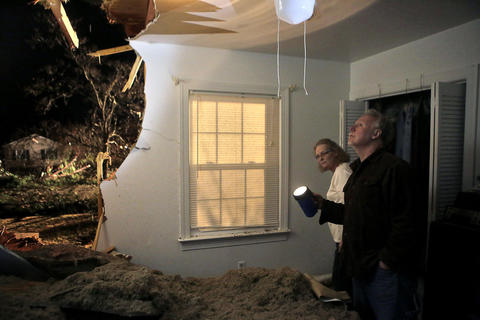 Roger and Nancy Minton inspect the damage for the first time after a tree fell into their home during Friday evening's severe weather.