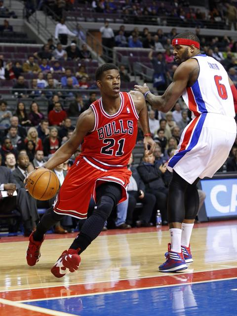 Jimmy Butler dribbles around the Pistons' Josh Smith in the first quarter.