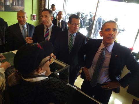 President Barack Obama, looks to the menu board before placing his order. Obama brought a group of governors into Cafe Beauregard, a New Britain restaurant, for a quick lunch. With the President, from left, are Massachusetts Gov. Deval Patrick,Vermont Gov. Peter Shumlin, and Gov. Dannel P. Malloy.