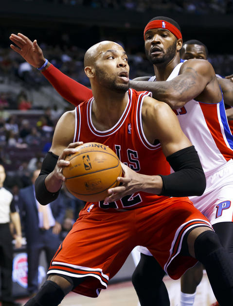 Taj Gibson is defended by the Pistons' Josh Smith in the second quarter.