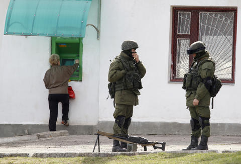 A woman stands near an ATM machine as uniformed men, believed to be Russian servicemen, are seen in the foreground near a Ukrainian military base in the village of Perevalnoye.