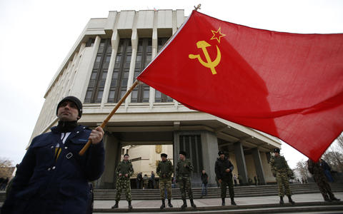 A man holds a Soviet Union flag as he attends a pro-Russian rally at the Crimean parliament building in Simferopol.