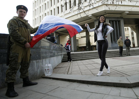A woman poses for a picture next to a member of the Crimean self-defencs unit during a pro-Russian rally at the Crimean parliament building.