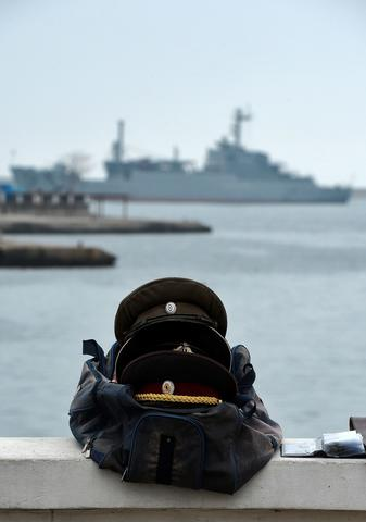 "Old military paraphernalia is sold on the side of the harbour in Sevastopol, as the Russian navy seagoing armament transport ""General Ryabikov"" is stationed in the background."