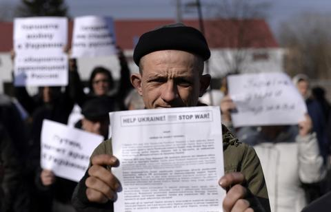 "A man holds a placard reading ""Help Ukraine ! Stop war !"" during an anti-war rally in front of the Russian embassy in Kiev."