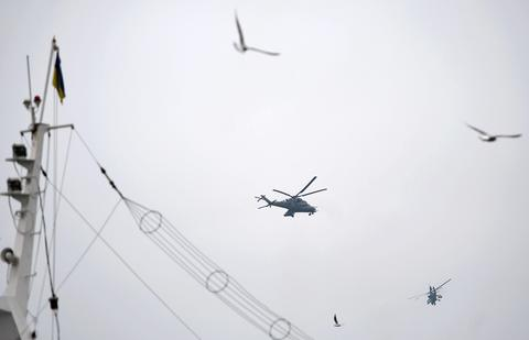 Two Russian Mi24 military helicopters fly over a ship bearing the Ukranian flag in the harbour of Sevastopol.