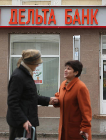 People walk past a branch of Delta Bank on March in Simferopol. Banks in Ukraine have begun imposing limits on the amount of money individuals can withdraw per day, and both the Ukrainian hryvnia and the Russian rouble have fluctuated strongly against western currencies.
