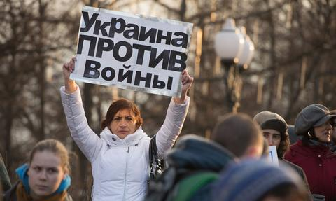 "A woman holds a poster reading ""Ukraine against war !"" during a pro-Ukrainian rally in Moscow on March 7."