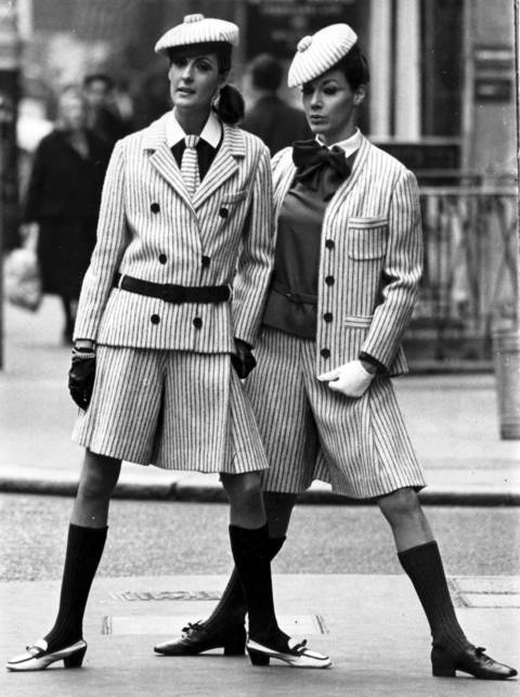 """Two London birds wear Christian Dior's striped suits, short and narrow, with emphasis on the hips. Suit at left is navy and white pin stripes, with navy blouse, pleated culottes, and horizontally striped tie. The cardigan version is in red and white stripes with scarlet socks and blouse."""