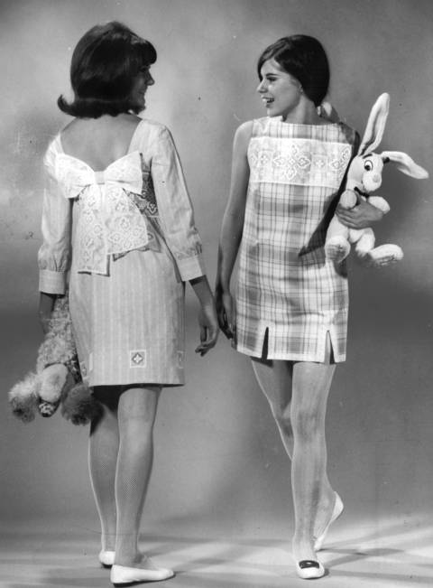 """Venetian lace is used for this pair. Pam Kimmell, left, Wheaton high school, wears a short dress of turquoise and white lawn ($35), trimmed with giant bow and cut-outs at hemline. Teri's blue on white plaid cotton skimmer ($22.95) features wide band of lace and narrower lace edging at hem."""