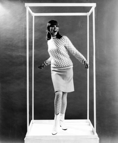 """Kicky checkerboard pattern of the crew necked pullover (about $16) banded with two-tone stripes at hips, cuffs and neck is echoed in the high socks. Welt seamed skirt (about $11) is an easy A line."" And, of course, white go-go boots, another Mary Quant innovation. 1965."