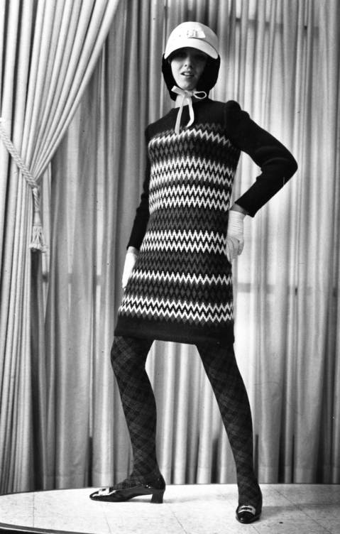 """Bolder than ever conception of a total look comes from Yves St. Laurent, youngest member of the Paris couture. He's extended the red, white and blue chromatic scheme in this sweater dress with zigzags of the three colors. Argyle wool stockings combine muted blue and red; white leather cap with attached snood of black beaver has brass buckle, as do patent leather, chunky-heeled shoes. Model is Carol Robins of Aquinas Dominican High school."""