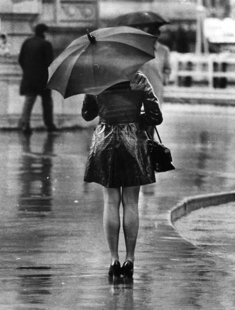 """A windswept rainy fall day in Chicago, but fashion prevails come wind or high water. Only the maxi-coat seems to offer protection from the elements, but the attention of girl-watchers makes the mini the choice of most young women."""