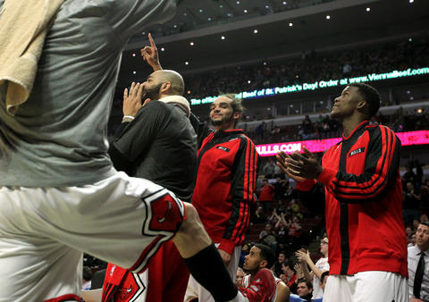 Carlos Boozer, Joakim Noah, and Jimmy Butler celebrate on the bench late in the fourth quarter.