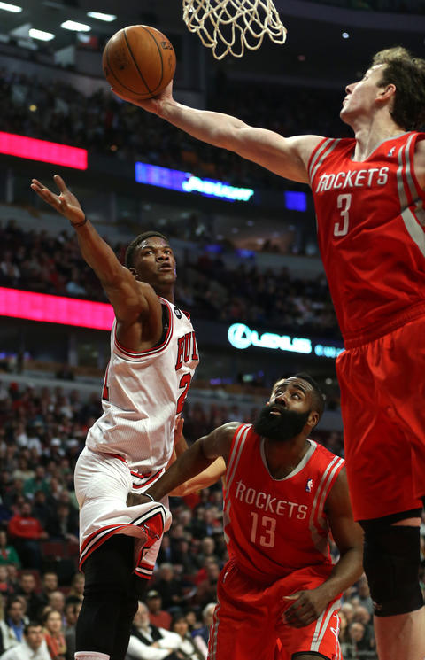 Jimmy Butler watches as the Rockets' Omer Asik pulls down a rebound in the first half.