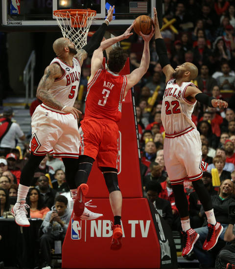 Taj Gibson blocks the shot of the Rockets' Omer Asik in the first half.