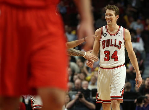 Mike Dunleavy is congratulated by teammate Carlos Boozer (blocked at left) after Dunleavy threw a full court pass to Jimmy Butler at the end of the first quarter.