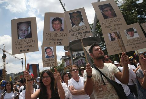 CARACAS, VENEZUELA - FEBRUARY 28: Protesters hold up photos of people they say were assassinated, during an anti-government demonstration on February 28, 2014 in Caracas, Venezuela. Almost three weeks after protests began, demonstrators continued to block thoroughfares and clash with security forces.