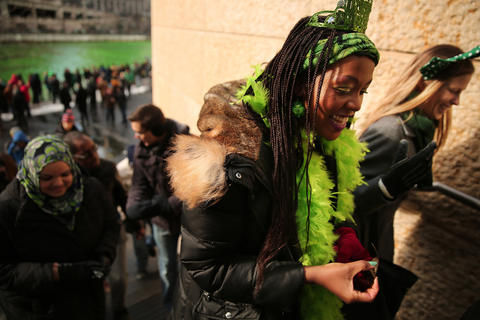 Dressed in green Nyamu Makhuvha of South Africa laughs with friends after watching members of the Chicago Journeymen Plumbers Local Union 130 pour green dye into the Chicago River as part of the annual St. Patrick's Day festivities.