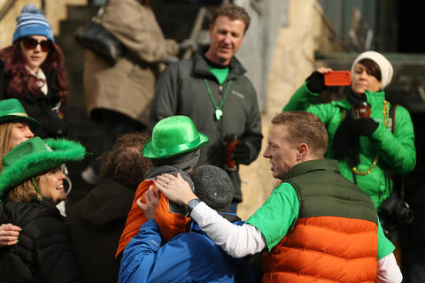 Families take photos after watching members of the Chicago Journeymen Plumbers Local Union 130 pour green dye into the Chicago River as part of the annual St. Patrick's Day festivities.