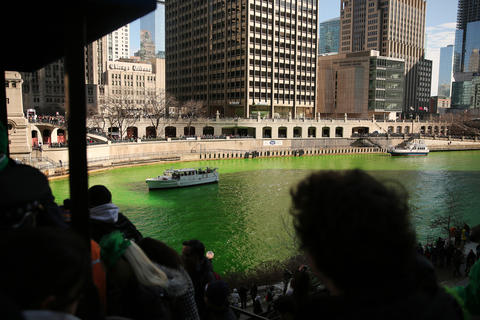 A crowd looks on after members of the Chicago Journeymen Plumbers Local Union 130 poured green dye into the Chicago River as part of the annual St. Patrick's Day festivities.