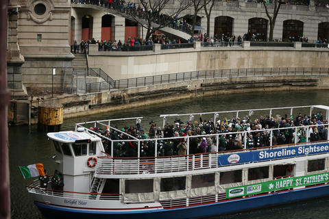 Guests aboard the Bight Star sightseeing ship wave to those on shore as members of the Chicago Journeymen Plumbers Local Union 130 prepare to pour green dye into the Chicago River as part of the annual St. Patrick's Day festivities.
