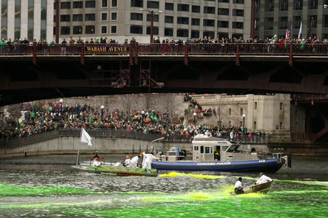 A crowd watches as members of the Chicago Journeymen Plumbers Local Union 130 pour green dye into the Chicago River as part of the annual St. Patrick's Day festivities.