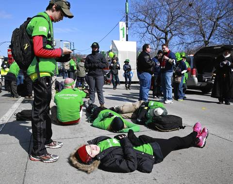 Julianne Reynolds of Fairhope, Alabama takes a nap with fellow parade participants before the St. Patrick's Day Parade on Columbus Drive, in Chicago.