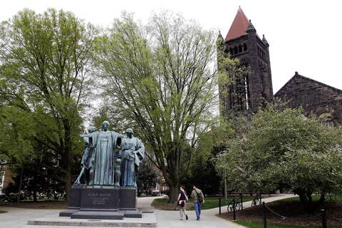People pass the Alma Mater statue on the University of Illinois campus in Urbana.
