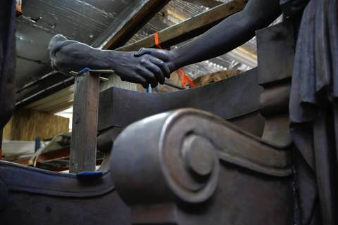 The hand of the Athena figure holds the disembodied hand of the iron worker.