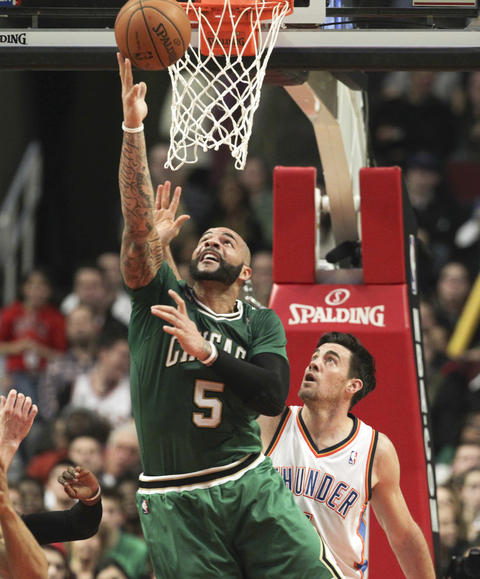 Carlos Boozer goes to the basket in front of the Thunder's Nick Collison during the second half.