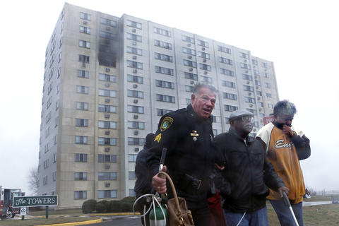 Staff Photo Of The Week: March 1-March 7, 2014   A Newport News police officer assists residents away from an apartment building in the 700 block of Waterfront Circle as Newport News firefighters respond to a fire Friday afternoon.
