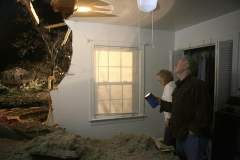 Photo Of The Week: Jan 10-Jan 17, 2014   Roger and Nancy Minton inspect the damage after a tree fell into their home in the Pinetta area of Gloucester County on Saturday evening.