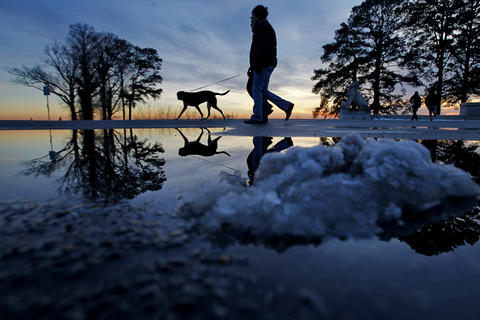 Staff Photo Of The Week: Feb 1-Feb 7, 2014 Patrik and Camilla Lasson walk their dog Roxy as snow piles melt while the sun sets Friday evening near Lions Bridge.